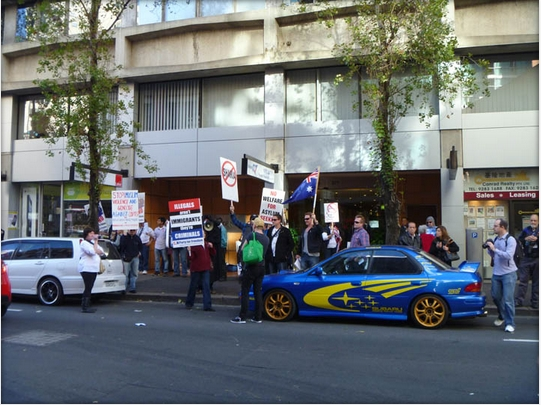 Thousands  Hundreds A few Muslim haters shivering outside an evil green socialist left-wing building with a blue car.