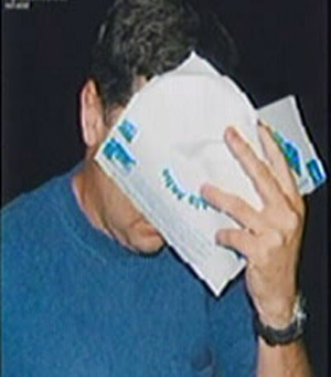 Gary Clark, husband of MP Jackie Kelly, hides behind the pamphlet.